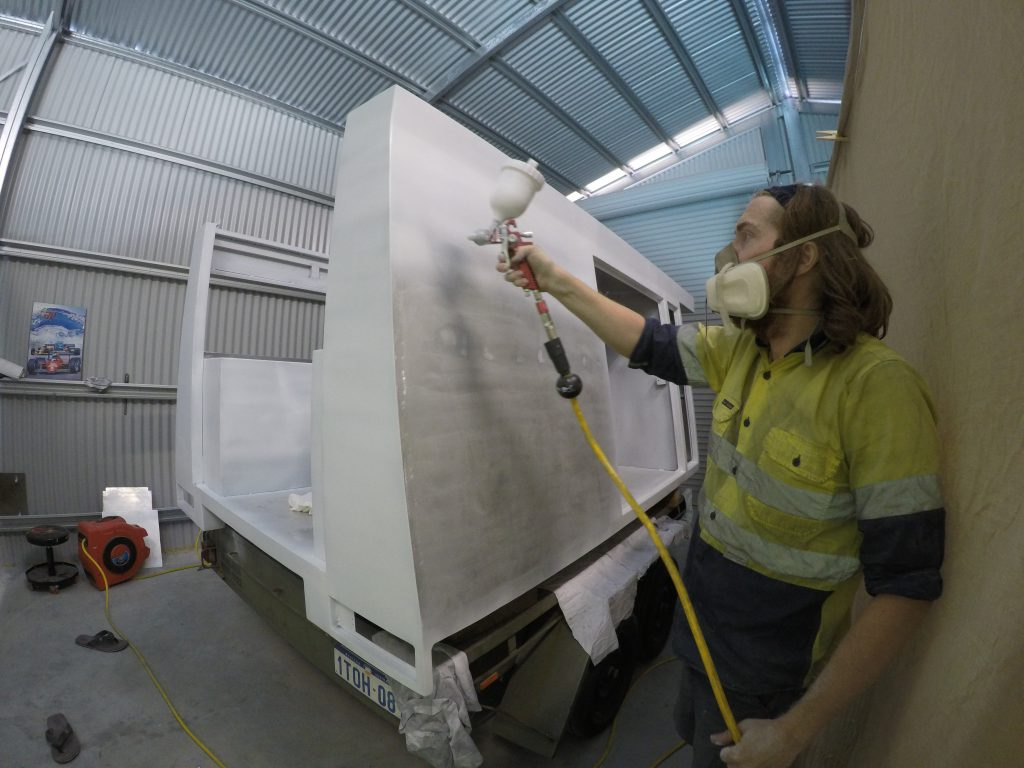 Photo of Cody priming the camper box with a top-loaded spray gun.