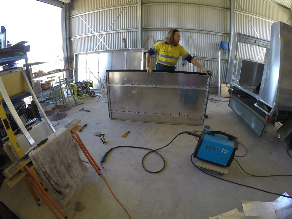 Photo of Cody test fitting the hinge on the reinforced kitchen door.